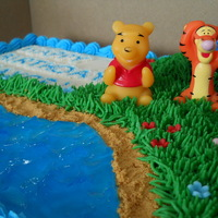 Winnie The Pooh Cake Winnie the Pooh cake with water, sand, grass and flowers. The figures were given to me, by the mother, to add to the cake as they are his...