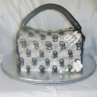 Dooney & Bourke Carved cake with hand piped logo.