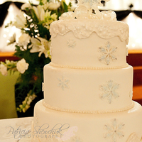 Winter Wedding Cake white fondant with very lightly dusted blue filigree snowflakes, isomalt baubles and and isomalt topper