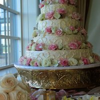 Mary's Romantic Wedding Cake Chocolate cake, chocolate mousse filling and buttercream icing. Scroll work and fresh pink and white roses cover this 4 tier wedding cake