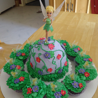Tinkerbell I made this cake for my great neice's 5th birthday. She loves Tinkerbell and purple. Flowers are made out of royal icing. Iced the...