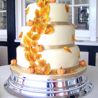 Autumn / Fall Leaves And Pumpkins 3 tiered stacked cake covered in Belgian white chocolate paste. Bottom tier, red velvet with cream cheese frosting, middle tier, chocolate...