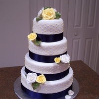 Wedding Cake With Roses And Ribbon Wedding cake with yellow dots, blue ribbon, and handmade sugar roses.