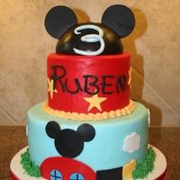 Mickey Mouse Cake  Covered in fondant with fondant accents. This was my first time using The Mat; what an amazing tool! The hat on top is a half sphere cake...