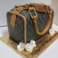 Designer Handbag Cake Frosted in pastry pride and covered with an edible image of the LV logo. All decorations are gumpaste and fondant