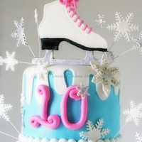 Ice Skating Cake Ice Skate Topper on a Winter Wonderland Cake with Snowflakes