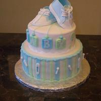 Baby Converse Shoe Cake This is a white cake with buttercream, for a baby boy baby shower. Hand made converse shoes out of gum paste.
