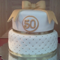 50Th Anniversary Cake Covered in fondant, quilted design, fondant bow and accents. Gold ribbon used around each tier.