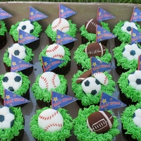 Sporty Birthday Cupcakes Chocolate cake with green grass buttercream frosting and topped with fondant baseballs, soccer balls, and footballs.