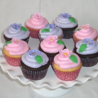 Tea Party Cupcakes Chocolate and vanilla cake with buttercream frosting topped with a fondant flower and a leaf.