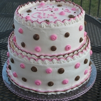 Baby Shower Cake White cake with fresh strawberry frosting covered in whip cream frosting and accented with pink and brown whip cream frosting dots.