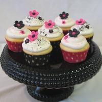 Pink & Black Flower Cupcakes White vanilla cake with vanilla buttercream frosting topped with hot pink and black fondant flowers and pink and black conffetti.