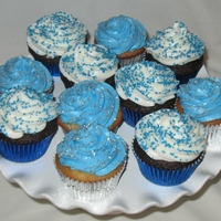 Ice Blue Holiday Cupcakes White and Chocolate cupcakes with buttercream frosting topped with metalic sprinkles. I created 100 of them for a christmas party.