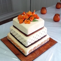 Fall Wedding Cake Bride wanted orange calla lillies, and fall inspired colors. The board is fondant treated to look like wood grain.