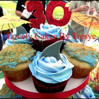 30 Bites Shark cupcakes and beach umbrellas. Shark fin is made from fondant