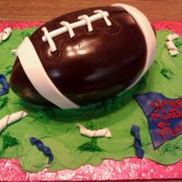Football Cake This cake is based on a Susan Carberry's design. It is a WASC yellow cake carved and covered in chocotate fondant with other fondant...