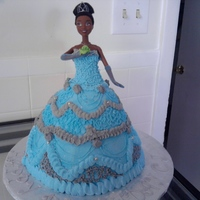 "Princess Tiana Doll Cake This cake is a WASC yellow cake baked in a glass measuring cup and there is a 10"" round on the bottom. The cake is all buttercream"