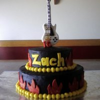 Zach's 15Th Black chocolate buttercream cake with flames and a guitar.