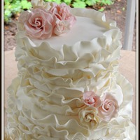 Ivory Wedding Cake With Fondant Ruffles And Pink Gum Paste Roses Ivory wedding cake with fondant ruffles and pink gum paste roses.