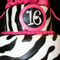 Zebra Stripes With Hot Pink Bow Fondant covered cake. I cut the zebra print out and glued it to the white fondant using vodka. The loop bow was made following a tutorial...