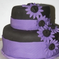 Purple And Black Peanut butter German Chocolate cake, with a peanut butter glaze, and buttercream. Covered in fondant.