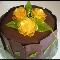 Rose Fantasy The cake is covered in chocolate frosting and is decorated with yellow roses made from Puller sugar. The cake is surrounded by chocolate...
