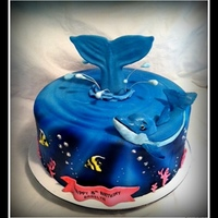 Dolphin Themed Birthday Cake Cake designed around party plates. Airbrushed same scene from plates onto cake then added dolphin and tail made from fondant.
