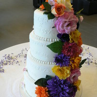Wedding Cake With Flower Cascade This cake is done in buttercream and artificial flowers provided by bride cascading from top to bottom. The Bride and groom had given me...