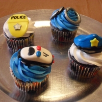 Police Themed Cupcakes Chocolate cupcakes with buttercream. Hand molded fondant toppers. Police badge, hat, car and handcuffs