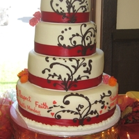 Red And White Buttercream icing, satin ribbons the scrolling is made with chocoate and the little flowers are made of gum paste
