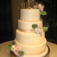 Ivory Wedding Cake cake is covered in buttercream, silk ribbon, two layers have buttercream lace. The flowers are gum paste