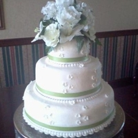 Wedding Cake Mint Green And White Cake is covered in butter cream, satin ribbons and gumpaste flowers. The cake topper is real flowers