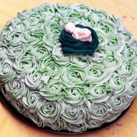 Rose Baby Shower Cake *Lighter green rose baby shower cake. Vanilla Butter cream with a white chocolate baby.