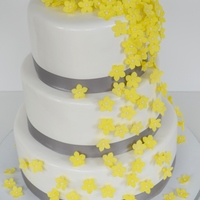 Yellow Flower Wedding Cake This is another version of my original yellow cascading flower wedding cake. Flowers are gumpaste and the ribbon is satin.