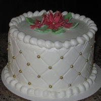 "Christmas Mini Cake 6"" round coverd in buttercream. Imprinted the quilt pattern and added gold pearls. Poinsettas made out of fondant."