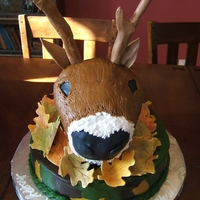 Deer Head All hand carved & covered with buttercream except antlers, ears & nose are fondant. head is sitting on a 10 inch round cake.
