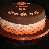 Chocolate Orange Petal Cake Chocolate cake with a hidden design of orange circles. Filled and covered in chocolate ganache and chocolate fondant, decorated with orange...