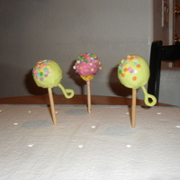 Baby Rattle Cake Pops Chocolate cake/icing, dipped in white chocolate and decorated with sprinkles and fondant handle