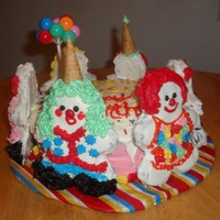 Clown Cake! Layered round cake, colored icings, and the clowns are decorated sugar cookies I made with a gingerbread man pan.