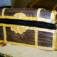 Treasure Chest full sheet cake divided into three sections and layered on top of each other iced and spayed like chest , add all the details . Spray woith...