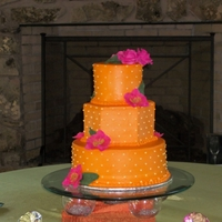 Tropical Themed Wedding Orange buttercream wedding cake with hot pink roses and orchids.