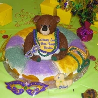 Mardi Gras Theme - King Cake Baby Shower Cake The king cake is chocolate cake and the bear is vanilla cake. The bead and mask are made out of fondant