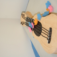 Ukulele Cake With Lei Flowers A customer ordered a ukulele cake with lei flowers. I carved the cake and decorated it in buttercream icing. The flowers are gum paste and...
