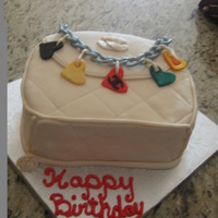 Chanel Bag   yellow cake/ vanilla custard filling covered in fondant. chain and charms made of gumpaste.TFL