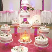 Alexis La Quinceanera Cake Tiered white and chocolate Tres Leches cakes filled with a vanilla mousse displayed on glass vases filled with pink water beads, led...