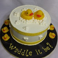 Waddle It Be? A Gender Reveal Cake!  White velvet cake (dyed PINK) with white chocolate IMBC. Ducks were purchased by client. All buttercream except border ribbon and cake drum...