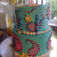 Sky Blue And Pink Paisley Tiers With Yellow Daisies Two tiers, iced in sky blue buttercream, pink paisley piped on, yellow daisies.