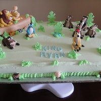 Lion King Cake   Cake was frosted with a buttercream icing and the figures were gumpaste and fondant. Tree accents are fondant & gumpaste.