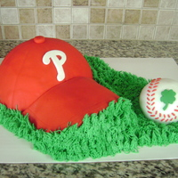 Phillies #1  This was a cake for a first birthday. Half chocolate and half yellow cake hat. Covered in fondant. Baseball is chocolate cake covered in...