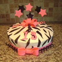 Zebra Cake   Half chocolate and half yellow cake. Buttercream icing. Bows, stars, numbers and zebra stripes made from fondant.